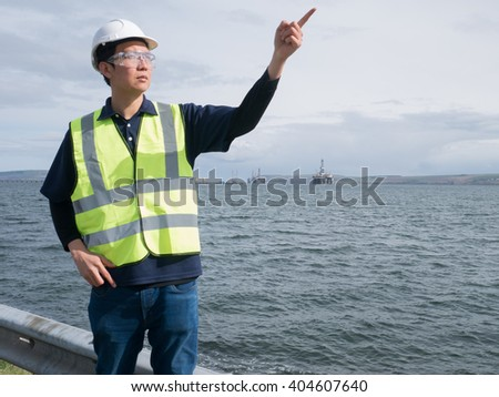 Asian engineer pointing and standing in front of semi submersible oil rig - stock photo