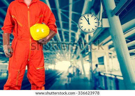 Asian engineers holding a yellow hardhat on abstract Blurred photo of sky train, transportation industrial concept - stock photo