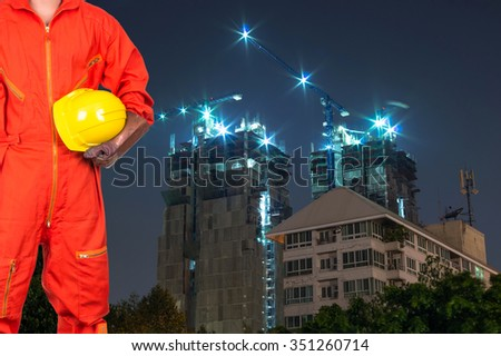 Asian engineers holding a yellow hardhat on construction site building at twilight time, industrial construction concept - stock photo