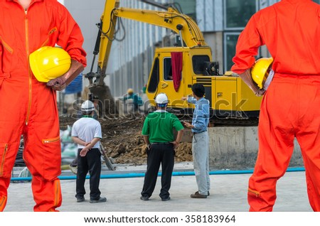 Asian engineers holding a yellow hardhat on construction site workers, industrial construction concept - stock photo