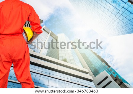 Asian engineers holding a yellow hardhat on Modern business building glass of skyscrapers, Business concept of architecture industrial concept - stock photo