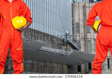 Asian engineers holding a yellow hardhat on photo blurred of construction site workers, industrial construction concept - stock photo
