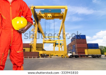 Asian engineers holding a yellow hardhat on Under construction four cranes with cloud on blue sky, construction industrial concept - stock photo