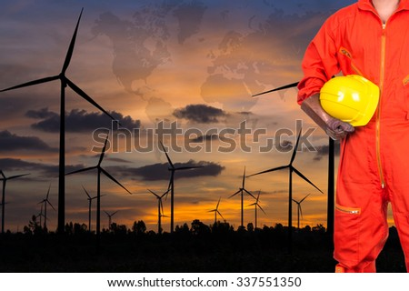 Asian engineers holding a yellow hardhat on Wind turbine power generator with world map at twilight time, industrial concept, Elements of this image furnished by NASA - stock photo