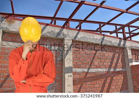 Asian engineers wiht yellow safety hemet on photo blurred of construction site.