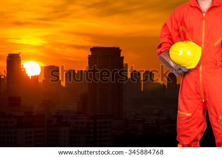 Asian engineers worker holding a yellow hardhat on Building of cityscape at sunrise background, industrial concept - stock photo