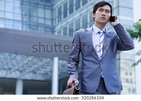 Asian entrepreneur talking on the phone when leaving airport