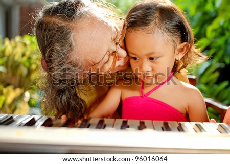 asian ethnic elderly woman love to teach child play piano - stock photo