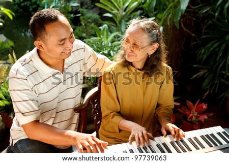 asian ethnic family portrait of elderly mother play piano together with young adult son