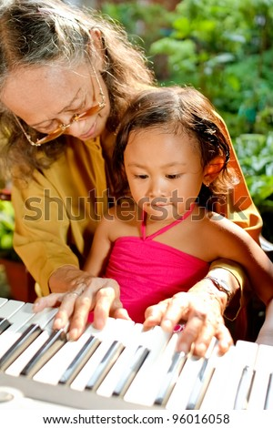 asian ethnic grandmother teach child playing piano - stock photo