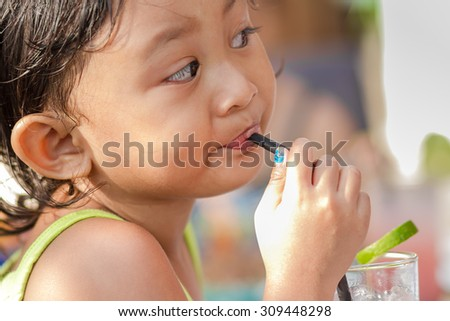 asian ethnic little girl enjoy drinking a glass of lemonade after swimming on hot summer day - stock photo