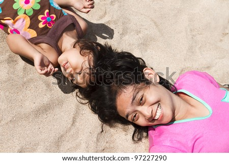 asian ethnic mom and child relaxing together on the beach - stock photo