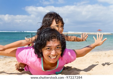 asian ethnic mother and child happy playing at the tropical beach - stock photo
