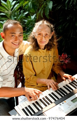 asian ethnic old mother play piano together with young adult son - stock photo