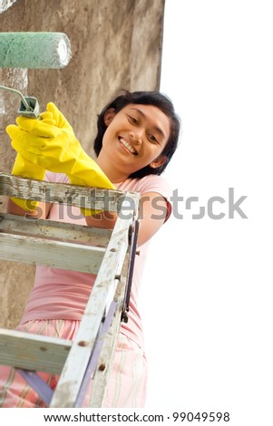 asian ethnic young woman with roller and ladder on painting work - stock photo