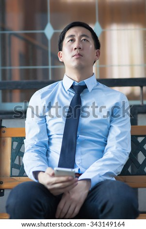 Asian exhausted businessman sitting in corporate building - stock photo