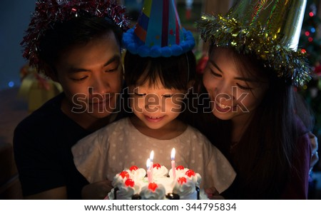 Asian family a birthday party for her daughter's daughter is about to blow out the candles. - stock photo