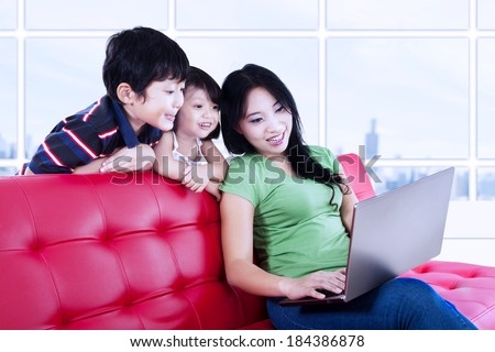 Asian family; a mother and kids browsing the internet together - stock photo