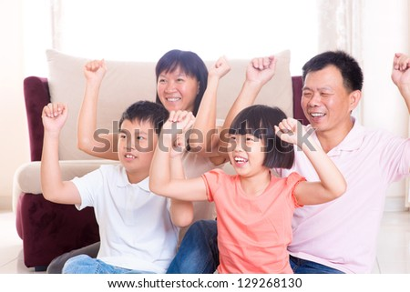 Asian family at home. Portrait of happy parents and children playing game arms raised together at home. - stock photo