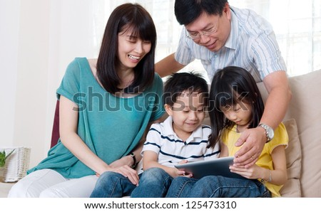 Asian family browsing internet on tablet computer - stock photo