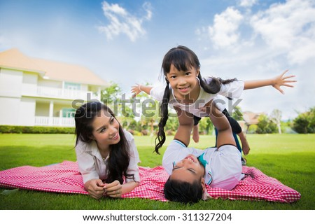 Asian family came to rest on the front lawn, father and daughter were teasing each other play and have fun and happy - stock photo