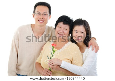 Asian family celebrates Mothers Day. Adult offspring giving carnation flowers to senior mother isolated on white. - stock photo