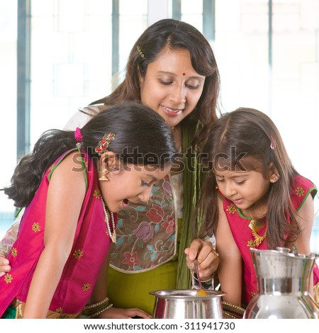Asian family cooking food together in kitchen. Indian mother and children preparing meal at home. Traditional India people with sari clothing. - stock photo