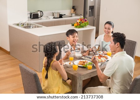 Asian family dining together in the kitchen - stock photo