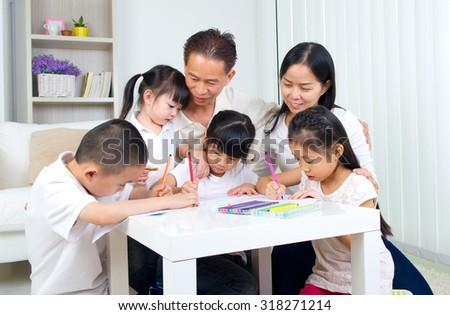 asian family doing school homework at living room - stock photo