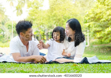 Asian family enjoying outdoor nature in the park - stock photo