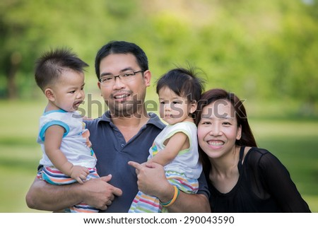 Asian family father, mother, boy and girl in park - stock photo