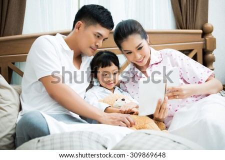 Asian family Fathers are teaching their children reading homework on the bed - stock photo