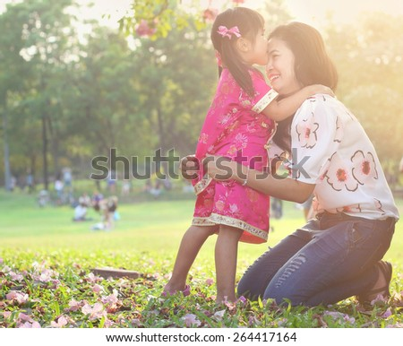 Asian family, Girls in cheongsam kissing her mather and laughing happily in park - stock photo