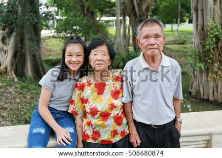Asian family group outdoor with grandmother , grandfather, girl and woman. , Multi-generation family having fun together outdoors concept.