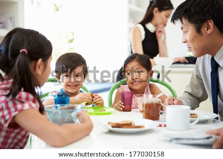 Asian Family Having Breakfast Before Husband Goes To Work - stock photo