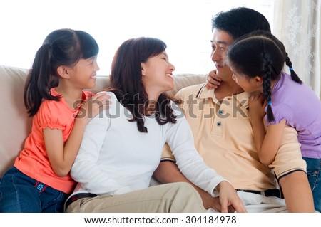 Asian family having conversation at home - stock photo