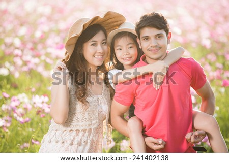 Asian family I bring my daughter to the park flower Cosmos - stock photo