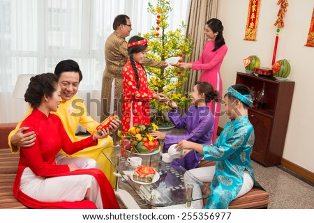 Asian family in ao dai dresses celebrating Tet at home