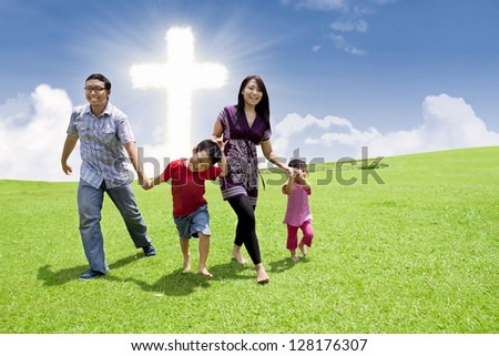 Asian family is having a stroll in a park by the Cross