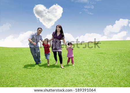 Asian family is having fun in the park under heart shape clouds - stock photo