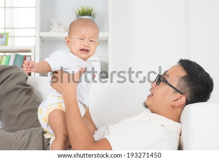 Asian family lifestyle at home. Father comforting crying baby boy. - stock photo