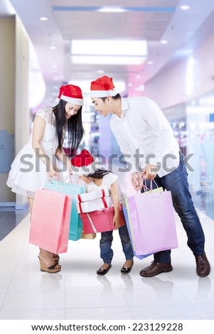 Asian family looking at shopping bags at the mall in christmas day - stock photo