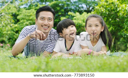Asian family looking up & smiling when lying on stomach and reading on grassland