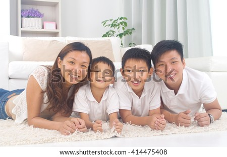 Asian family lying on the floor and smiling - stock photo