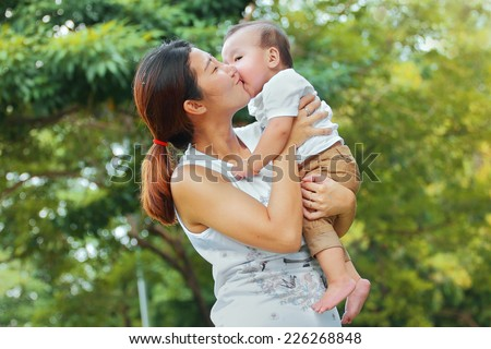 Asian family, Mother holding her baby was laughing in park - stock photo