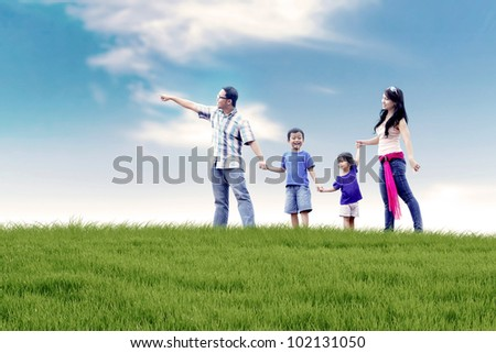 Asian family of father, mother, and two kids  having a quality time in meadow. Shot at summer - stock photo