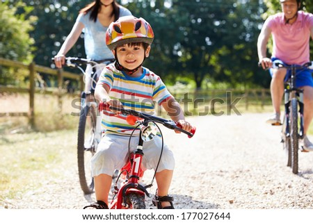 Asian Family On Cycle Ride In Countryside - stock photo
