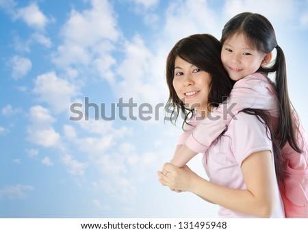Asian family outdoor fun. Asian mother piggyback her daughter at a nice summer outdoor - stock photo