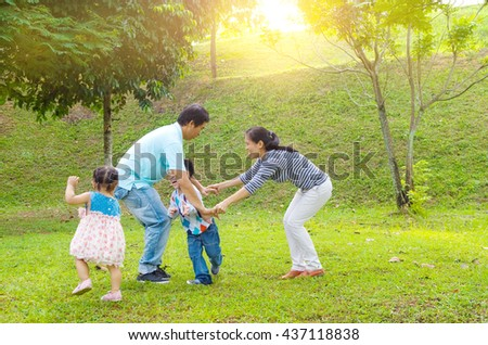 Asian family outdoor quality time enjoyment, asian people playing during beautiful sunset. - stock photo