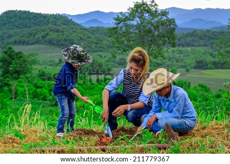 Asian family planting tree in farm near mountain